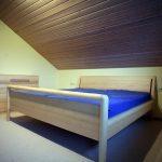Massivholzbett mit gebogenem Kopfteil und erhöhtem Fußteil