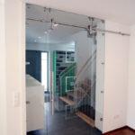 Ganzglas Schiebetüre als Trennung zwischen Garderobe und Wohnraum