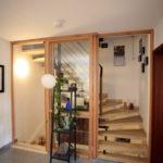 Holzrahmen mit Klarglas als Schiebetüren vor dem Treppenhaus