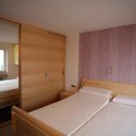 Schlafzimmer mit Spiegelschrank und passendem Bett